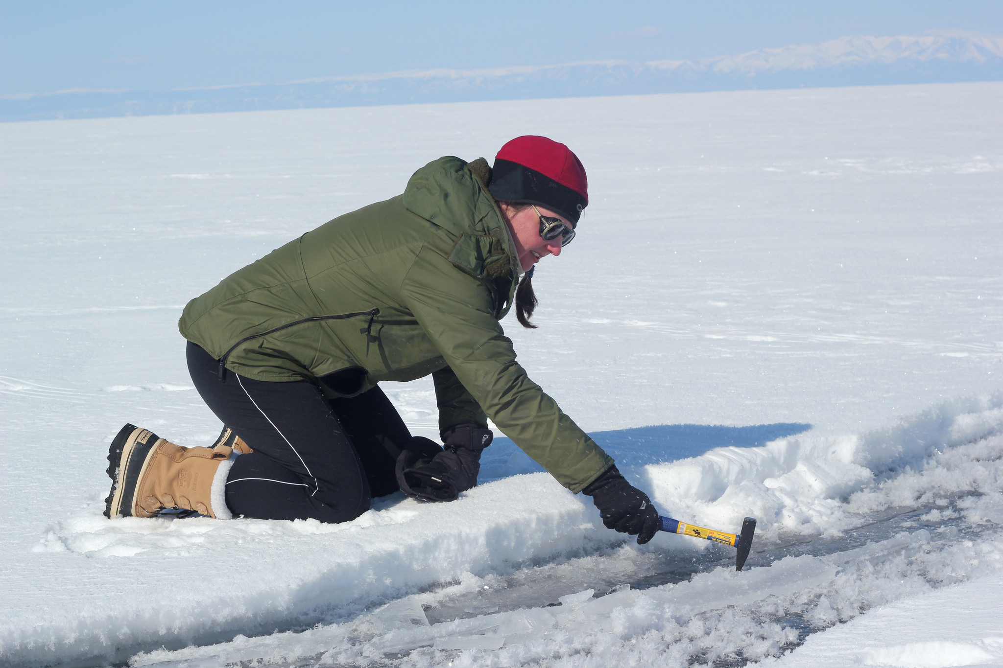 Laura is hammering the ice to get some fresh water to drink